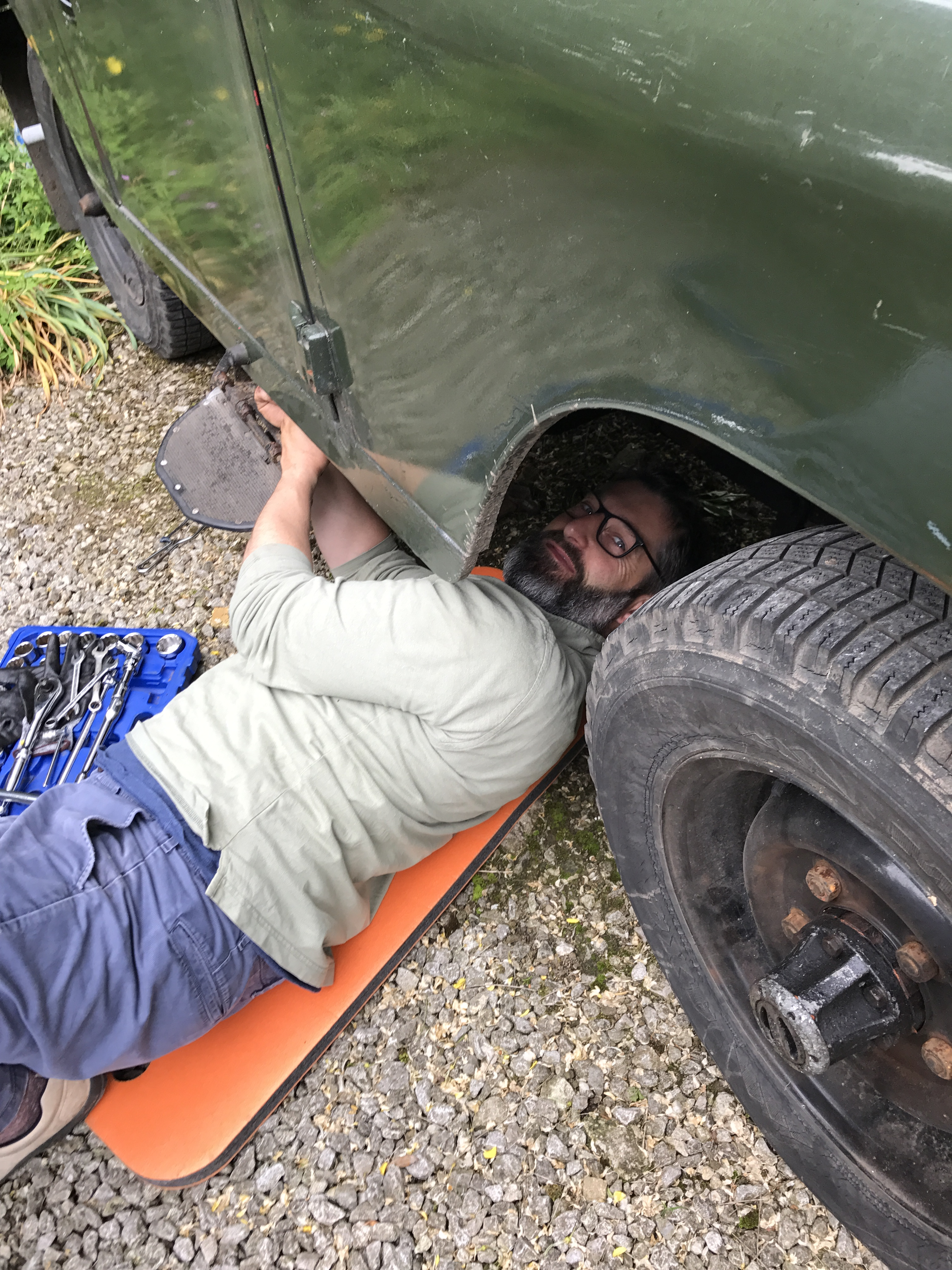 Andy lying underneath his classic Land Rover with tools as he prepares her for his next trip, mental health, wellbeing, mental strength, Andy's Landie, men's mental health